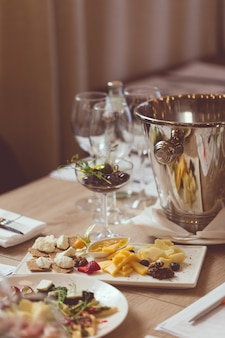 Cutlery, appetizers, spittoon and glasses on the wooden table in the restaurant.
