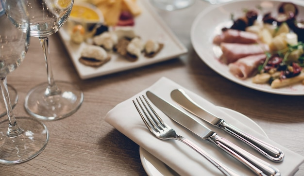 Cutlery, appetizers and wine glasses on the wooden table in the restaurant.