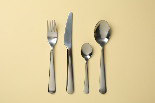 Cutlery on beige background, top view and space for text