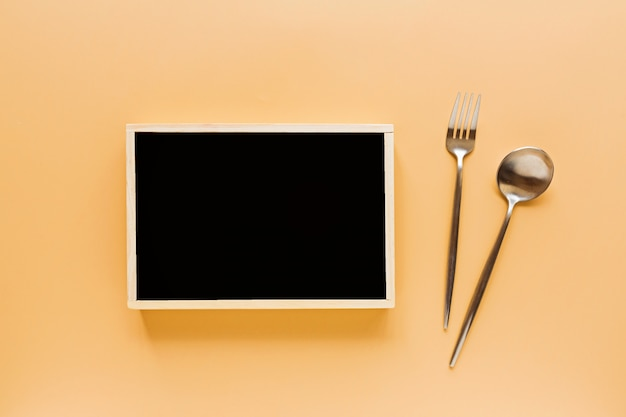 Cutlery and black chalk board on orange background