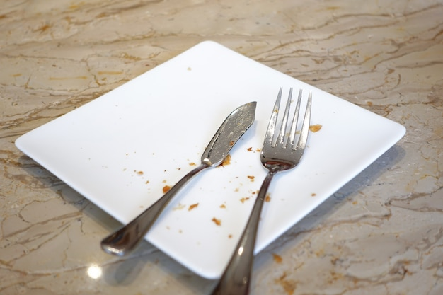 Cutlery and empty plate on wooden background