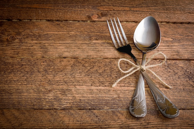 Cutlery fork and spoon on a wooden background