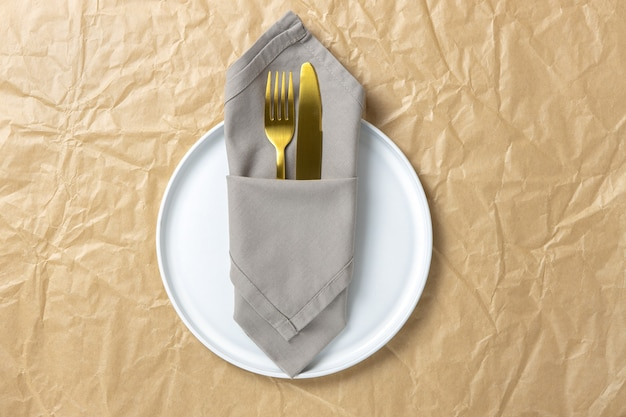 Cutlery, gold fork and knife in folded cloth napkin on white round plate on crumpled craft paper, minimal style flat lay, copy space.