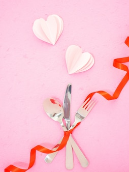 Cutlery and hearts on pink table