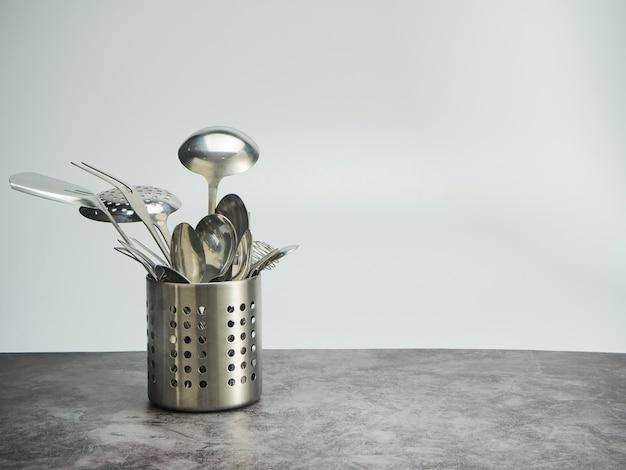 カトラリーホルダー、白い背景のテーブルにステンレス鋼