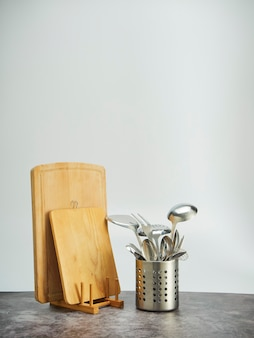 Cutlery holder, stainless steel and wooden cutting boards on table