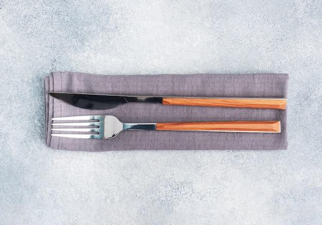칼 붙이 칼과 포크 냅킨, 회색 콘크리트 테이블, 복사 공간 평면도.