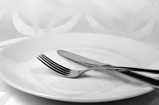 Столовые приборы, нож и вилка на тарелке