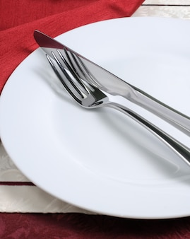 Столовые приборы (нож и вилка) на белой тарелке с салфеткой
