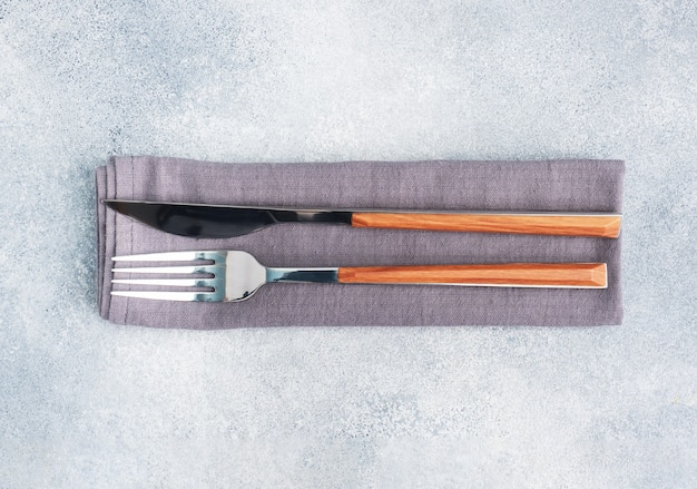 Cutlery knife and fork on a napkin, gray concrete table, copy space top view.