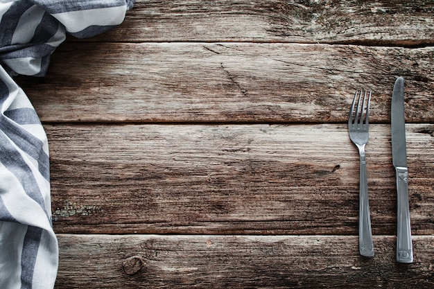 Cutlery and napkin frame on old wooden table