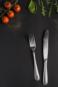 Cutlery near tomatoes and basil
