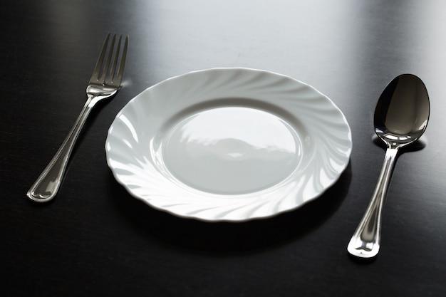 검정색 배경에 칼 붙이. 포크, 스푼, 나이프, 접시.