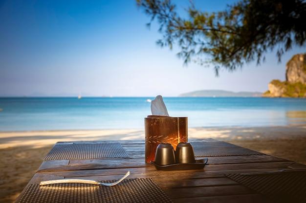 テーブルの上のカトラリー。砂浜と青い海に面した外。木からのコショウと塩。