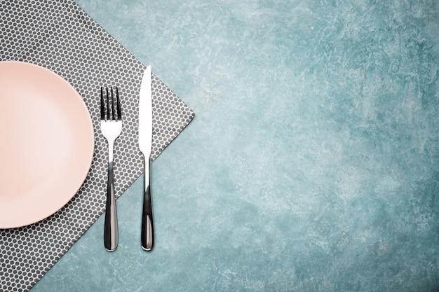 テーブルの上のカトラリー。ナプキンで皿、フォーク、ナイフ。
