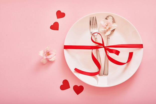 Cutlery and a plate with hearts on a pink surface for valentines day