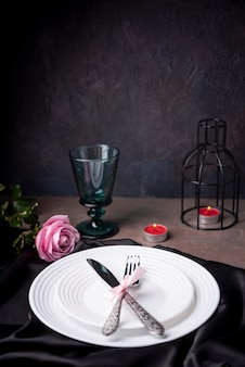 Cutlery on plates with rose and candles