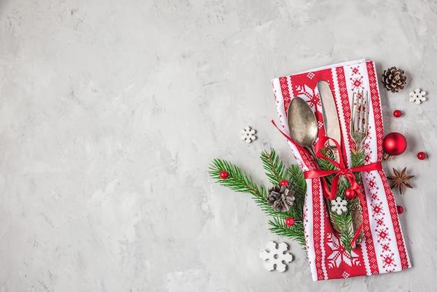 コピースペースのあるコンクリートのテーブルトップビューに休日の装飾が施されたクリスマスディナー用のカトラリーセット。フラットレイ。クリスマスの背景