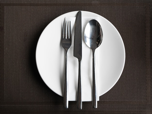 Cutlery set fork knife and spoon on white plate.