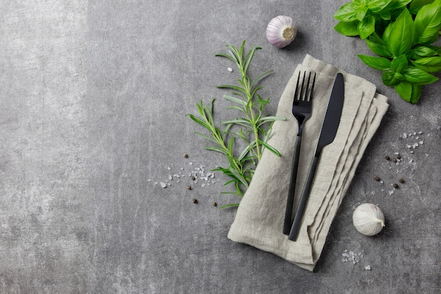 Cutlery set, stylish black cutlery and napkin with spice on dark background.