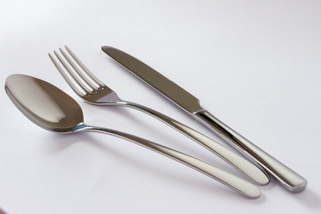 Набор столовых приборов с вилкой, ножом и ложкой, изолированных на белом фоне.