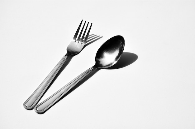 Cutlery set with fork and spoon isolated on pale white background