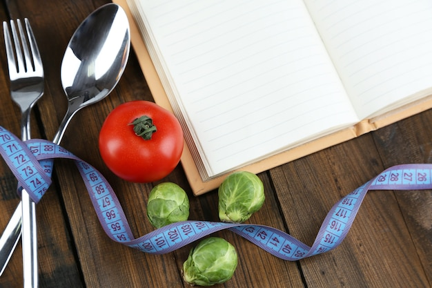 Столовые приборы, перевязанные измерительной лентой, и книга с овощами на деревянном столе