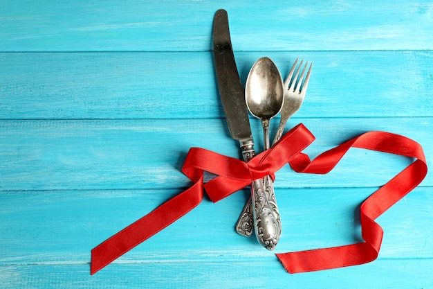 Cutlery tied with ribbon on wooden