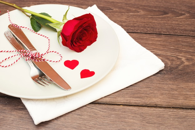 Cutlery with flower on plate above napkin