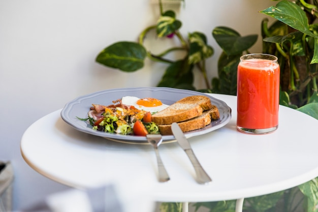 Cutlery with gray plate of breakfast and smoothies on round white table