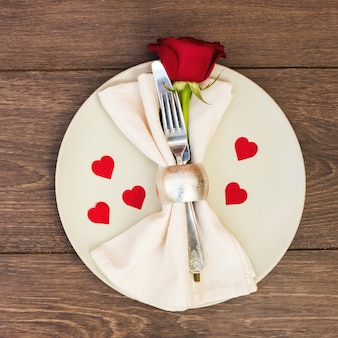 Cutlery with napkin and flower on plate
