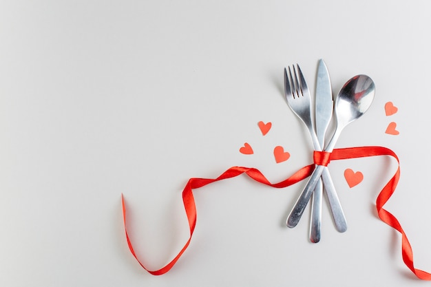 Cutlery with paper hearts on table