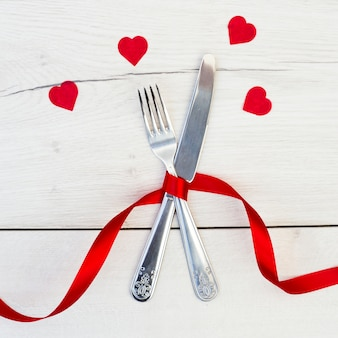 Cutlery with red ribbon near ornament hearts