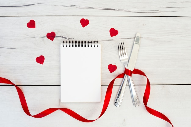 Cutlery with ribbon near ornament hearts and notebook