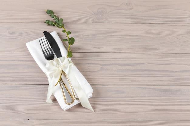 木製のテーブルにナプキンで包まれたカトラリー
