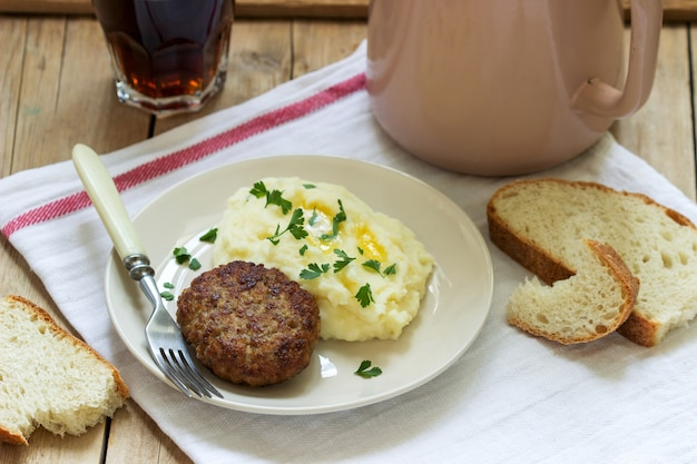 돈까스, 버터와 파슬리와 으깬 감자와 나무 테이블에 차.