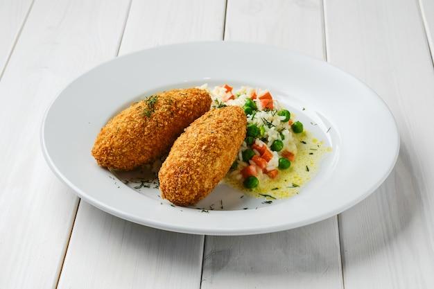 Котлета, фаршированная сыром, подается с рисом, зеленым горошком и морковью на белом деревянном столе