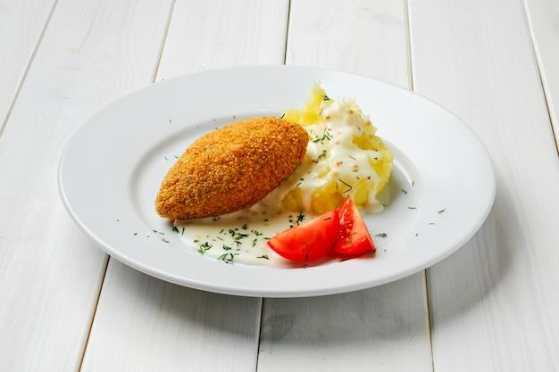 Котлета, фаршированная сыром, с картофельным пюре на белом деревянном столе