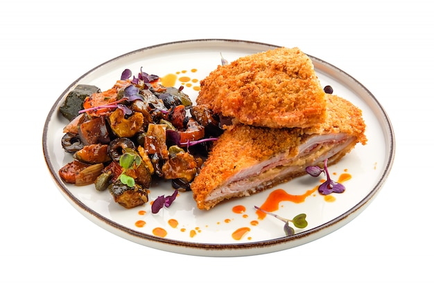 Cutlet with stuffing in breading with fried eggplant, olives and onion