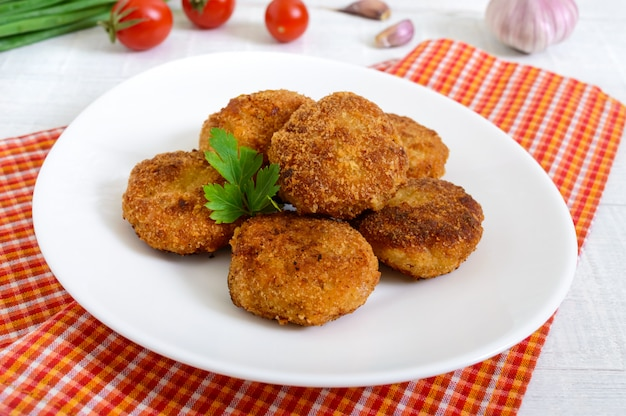Cutlets. juicy meat cutlets on a white plate on a wooden background.