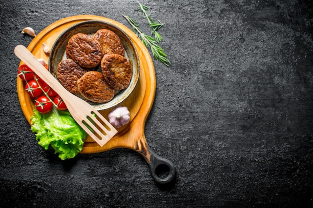 Cutlets at the old pan with a spatula, cherry tomatoes and salad leaves.