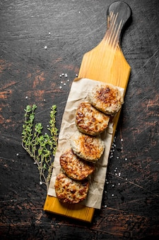 Cutlets on paper with thyme. on dark rustic