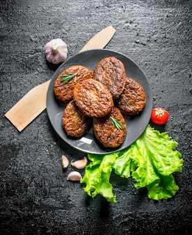 Cutlets on a plate with garlic, salad leaves and wooden spatula. on black rustic background