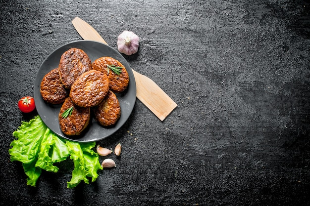 Cutlets on a plate with garlic, salad leaves and wooden spatula