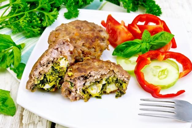 Котлеты, фаршированные шпинатом и яйцом, салат с помидорами, огурцом и перцем в блюде на полотенце, базилик и петрушка на фоне деревянной доски