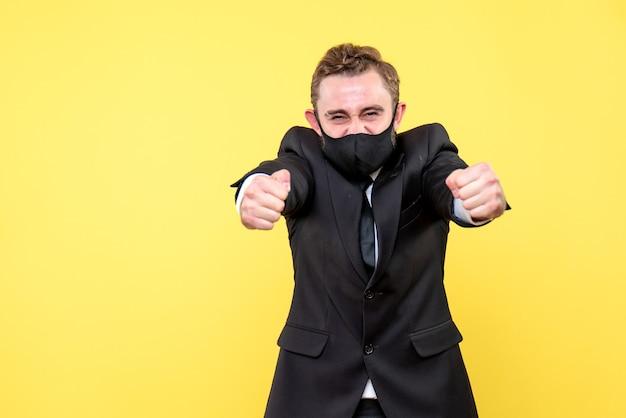 Ritaglio dell'uomo d'affari oberato di lavoro e stressato in piedi sul giallo