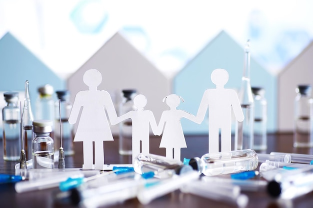 Cutout paper chain family with the protection of cupped hands, concept for security and care. hands with cut out paper silhouette on table. family care concept
