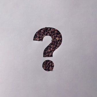 Cutout question mark in a sheet of grey paper revealing roasted coffee beans behind in a conceptual image with copy space