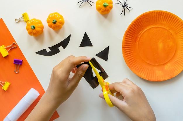 Отрезы бумаги для хэллоуина. бумага ручной резки. тыквы. ножницы и клей. на светлом фоне. вид сверху. плоская планировка. сделай сам. шаг за шагом