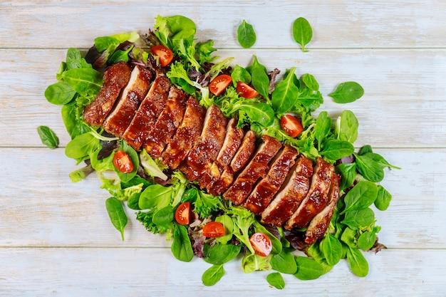 Филе свиной вырезки подается с зеленым салатом и помидорами.